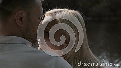 Στοργικό ζευγάρι φιλί που κάθεται σε μια προβλήτα κοντά στο ποτάμι Κοντινό απόθεμα βίντεο