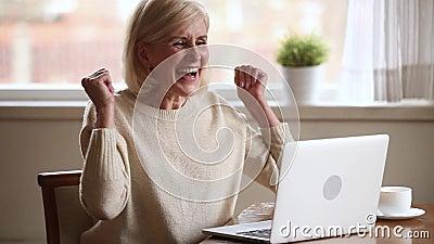 Συγκινημένη ανώτερη γυναίκα που αισθάνεται το νικητή που διαβάζει τις καλές σε απευθείας σύνδεση ειδήσεις απόθεμα βίντεο