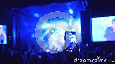 Συναυλία βράχου, βλαστός ακροατηρίων ανεμιστήρων στην κινητή τηλεφωνική απόδοση της μουσικής ομάδας σχετικά με λαμπρά το φωτισμό  φιλμ μικρού μήκους