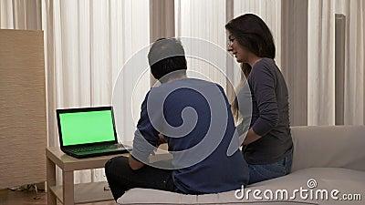 Συνεδρίαση ζευγών χαμόγελου στην άκρη του κρεβατιού που εξετάζει ένα lap-top με την πράσινη οθόνη ενώ έχοντας μια μεγάλη συνομιλί απόθεμα βίντεο