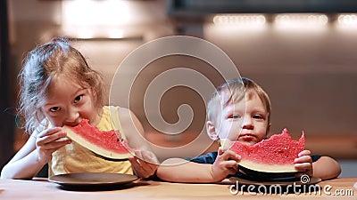Συνεδρίαση αδελφών και αδελφών στον πίνακα στην κουζίνα Αγόρι και κορίτσι που τρώνε το juicy καρπούζι, που κοιτάζει στη κάμερα απόθεμα βίντεο