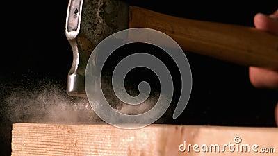 Σφυρί που χτυπά ένα καρφί στην ξύλινη σανίδα φιλμ μικρού μήκους