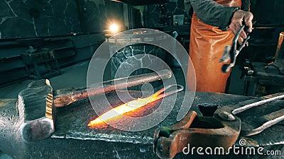 Σφυρηλατήστε τον εργαζόμενο βάζει το καυτό μαχαίρι στο αμόνι απόθεμα βίντεο