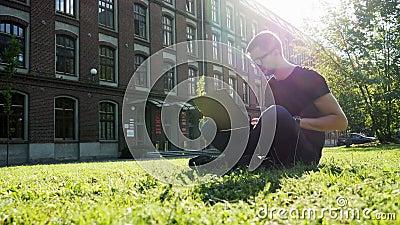 Σύγχρονος άνδρας φοιτητής ή ελεύθερος επαγγελματίας που εργάζεται σε φορητό υπολογιστή, που κάθεται σε ένα πάρκο σε πράσινο γκαζό απόθεμα βίντεο
