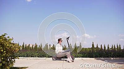 Σύγχρονος υπάλληλος γραφείου σε αστικό τοπίο Ελκυστικό μικρό κορίτσι κάθεται σε ένα ηλεκτρικό σκούτερ σε ένα πάρκο φιλμ μικρού μήκους