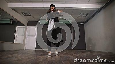 Σύγχρονος χορός χορού νέων κοριτσιών στα μαύρα ενδύματα Ο χορευτής κάνει τις γρήγορες και ενεργές μετακινήσεις των όπλων και των  φιλμ μικρού μήκους