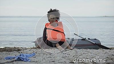 Ταραγμένη νεαρή κοπέλα με σωσίβιο κάθεται κοντά στη βάρκα, οι πρόσφυγες επέζησαν από τη συντριβή της βάρκας φιλμ μικρού μήκους