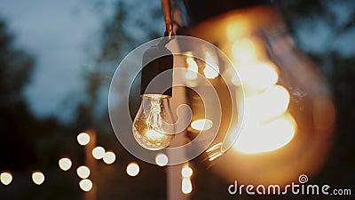 Τα διακοσμητικά εγχόρινα φώτα του φεστιβάλ κρέμονται και λάμπουν σε εξωτερικό χώρο τη νύχτα φιλμ μικρού μήκους