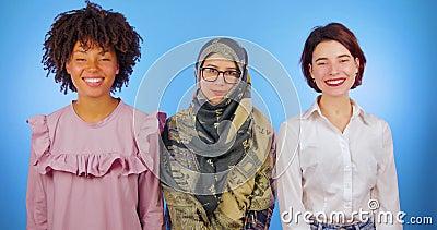 Τα μουσουλμανικά, αφρικανικά και ευρωπαϊκά κορίτσια που απομονώνονται εξετάζουν τη κάμερα, internationality, μπλε υπόβαθρο, φιλία απόθεμα βίντεο