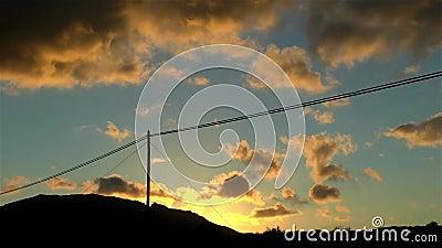 Τηλεφωνική γραμμή ενάντια στον μπλε και πορτοκαλή ουρανό στο ηλιοβασίλεμα με την κίνηση των ζωηρόχρωμων σύννεφων απόθεμα βίντεο