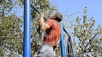Το άτομο τραβιέται επάνω στο φραγμό Αθλητισμός παιχνιδιού στο καθαρό αέρα Σπιτικός οριζόντιος φραγμός στο κατώφλι φιλμ μικρού μήκους