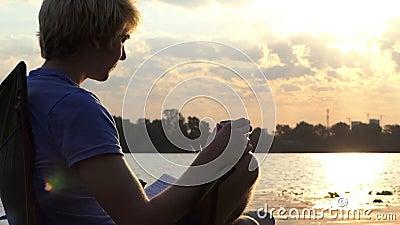 Το έξυπνο άτομο πίνει τον καφέ σε μια διπλώνοντας έδρα με το σημειωματάριό του στο ηλιοβασίλεμα στην slo-Mo φιλμ μικρού μήκους