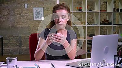 Το έξυπνο καυκάσιο θηλυκό πιπεροριζών χρησιμοποιεί το τηλέφωνό της καθμένος ήρεμα στον εργασιακό χώρο της, περιστασιακός δημιουργ απόθεμα βίντεο