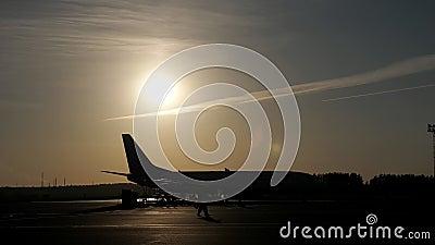 Το αεροπλάνο αρχίζει την κίνηση στο διάδρομο προσγείωσης διαδρόμων και άδειας εργαζομένων, σκιαγραφίες στο ηλιοβασίλεμα απόθεμα βίντεο