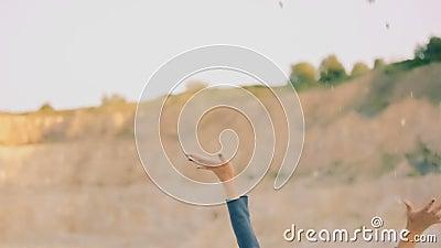 Το ευτυχές κορίτσι στις υπερβολικές πέτρες ρίψης ενδυμάτων ξυπόλυτες σε έναν αμμώδη δρόμο και έχει τη διασκέδαση απόθεμα βίντεο