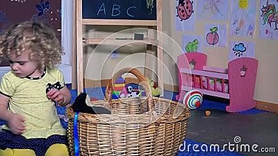 Το καλό παιδί μικρών κοριτσιών έβαλε όλα τα παιχνίδια στο ψάθινο καλάθι Το παιδί καθαρό καθαρίζει επάνω το δωμάτιο φιλμ μικρού μήκους
