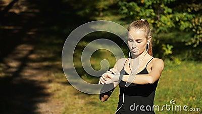 Το κορίτσι εξετάζει το ρολόι απόθεμα βίντεο