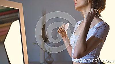 Το κορίτσι κάνει μασάζ και κάνει μια γκριμάτσα μπροστά στον καθρέφτη στο σπίτι χρησιμοποιώντας μασάζ από χαλαζία, φυσική πέτρα Αν απόθεμα βίντεο