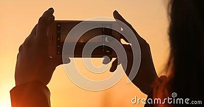 Το κορίτσι παίρνει μια εικόνα ενός όμορφου ηλιοβασιλέματος σε ένα κινητό τηλέφωνο απόθεμα βίντεο