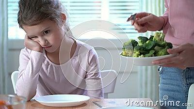 Το μικρό κορίτσι δεν θέλει να φάει τα λαχανικά και να αντιπαθήσει το γούστο του μπρόκολου και του σπανακιού απόθεμα βίντεο