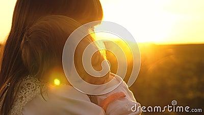 Το μικρό παιδί έπεσε κοιμισμένο στα όπλα της μητέρας, του περιπάτου mom και της κόρης του στο ηλιοβασίλεμα στο πάρκο το καλοκαίρι απόθεμα βίντεο