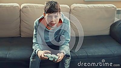 Το νεαρό αγόρι πριν την εφηβεία παίζει κονσόλα βιντεοπαιχνιδιών, διασκεδάζει, γελάει, κρατά το joystick. απόθεμα βίντεο