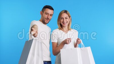 Το νεαρό ευτυχισμένο ζευγάρι που κρατά τσάντες για ψώνια απολαμβάνει την αγορά του απομονωμένο σε μπλε φόντο απόθεμα βίντεο