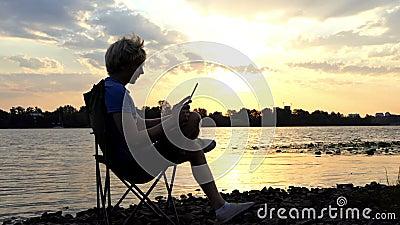 Το ξανθό άτομο κάθεται σε μια διπλώνοντας έδρα και εξετάζει το PC ταμπλετών του στο ηλιοβασίλεμα φιλμ μικρού μήκους