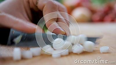 Το τέμνον κρεμμύδι μαγείρων σε έναν ξύλινο τεμαχίζοντας πίνακα closeup απόθεμα βίντεο