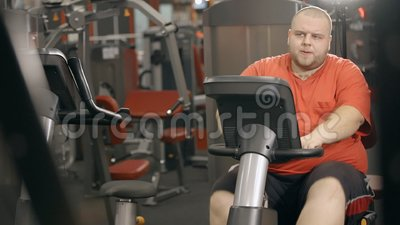 Το υπέρβαρο άτομο εκπαιδεύει στο ποδήλατο στη λέσχη ικανότητας φιλμ μικρού μήκους