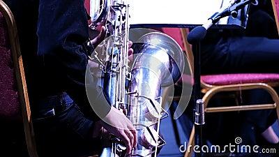 Το χέρι ενός άντρα με μαύρο κοστούμι σε ένα μεγάλο σαξόφωνο σε ένα τζαζ συγκρότημα Μουσικός ορχήστρας Εορταστική συναυλία του φιλμ μικρού μήκους