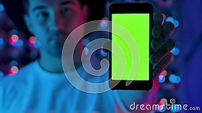 Το χέρι του δημιουργού κρατά ένα κινητό τηλέφωνο με το προσχέδιο της κάθετης πράσινης οθόνης απόθεμα βίντεο