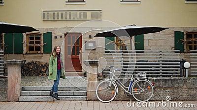 Το όμορφο κορίτσι με πράσινο παλτό φεύγει από την ταράτσα του εστιατορίου και πηγαίνει στο ποδήλατο Γερμανία Βαυαρία απόθεμα βίντεο