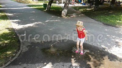 Το όμορφο κορίτσι πηδάει σε μια λίμνη στο δρόμο απόθεμα βίντεο