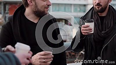 Τρία όμορφα άτομα με τις γενειάδες που έχουν τη συνομιλία και τον καφέ έξω Αργό MO φιλμ μικρού μήκους
