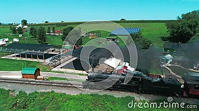 Τραίνο ατμού που ξεφυσά εμπρός από τις διασκεδάσεις στην επαρχία Amish όπως βλέπει από τον κηφήνα απόθεμα βίντεο