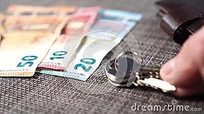 Τραπεζογραμμάτια ευρώ με καφέ πορτοφόλι και μεταλλικά κλειδιά για το διαμέρισμα σε γκρι τραπέζι απόθεμα βίντεο