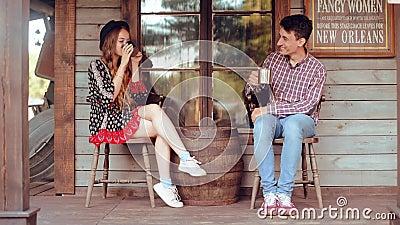 Τσάι/καφές κατανάλωσης ζεύγους στην άγρια δύση, στο δυτικό σπίτι Κορίτσι στο καπέλο με μακρυμάλλη Χαμόγελο κοριτσιών και αγοριών, απόθεμα βίντεο