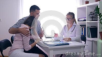 Υγεία γυναικών, ματαιωμένο ζεύγος με τη συνεδρίαση προβλήματος στειρότητας μπροστά από το θηλυκό γιατρό τους στο ιατρικό γραφείο απόθεμα βίντεο
