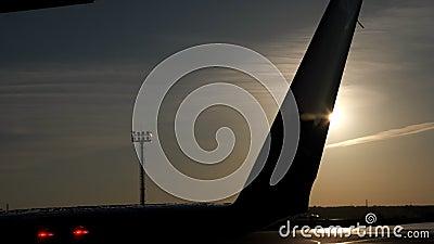 Υγρή ουρά των αεροσκαφών στον πύργο διαδρόμων και ραντάρ στην απόσταση στο ηλιοβασίλεμα απόθεμα βίντεο