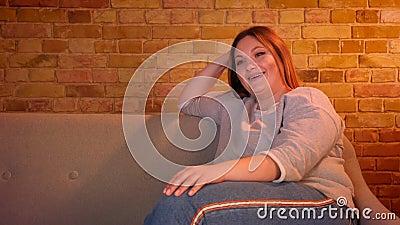 Υπέρβαρη μακρυμάλλης γυναίκα σπουδαστής που προσέχει τη TV με το μεγάλες ενδιαφέρον και τη διασκέδαση στην άνετη εγχώρια ατμόσφαι απόθεμα βίντεο