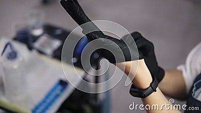 Υψηλής γωνίας υλικό από θηλυκό αφεντικό τατουάζ βάζει μαύρα λαστιχένια γάντια και ετοιμάζεται να κάνει ένα τατουάζ για τον πελάτη απόθεμα βίντεο