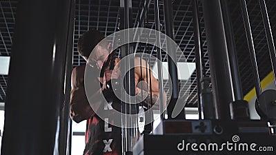 Φίλαθλο άτομο στους hoody ασκώντας triceps μυς στη γυμναστική με pull-down τις συνδέσεις μηχανών εξοπλισμού ικανότητας σχοινιών απόθεμα βίντεο