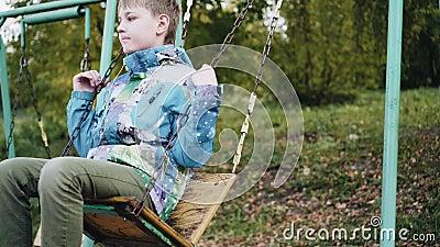 Φθινόπωρο Παιδική χαρά Αγόρι που κουνιέται σε μια κούνια Παιδική ψυχαγωγία απόθεμα βίντεο