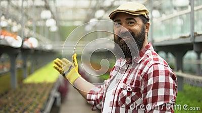 Φιλικός αγρότης που χαμογελάει στην κάμερα και δείχνει το φαινόμενο του θερμοκηπίου, επιτυχημένες επιχειρήσεις απόθεμα βίντεο