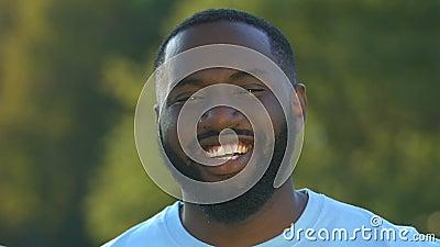 Φιλικός αφρο-αμερικανός άντρας που ψάχνει για κάμερα και χαμογελαστή, επιτυχημένη επιχείρηση φιλμ μικρού μήκους