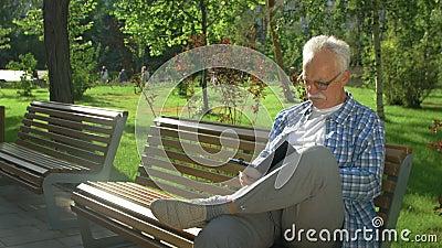 Φιλικός όμορφος γέρος με ebook στο πάρκο φιλμ μικρού μήκους