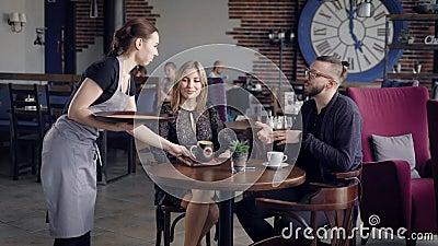 Φιλόξενο νέο φέρνοντας ποτό σερβιτορών στην καφετιά κεραμική κούπα στον πίνακα για τη γυναίκα Συνεδρίαση ζεύγους απόθεμα βίντεο