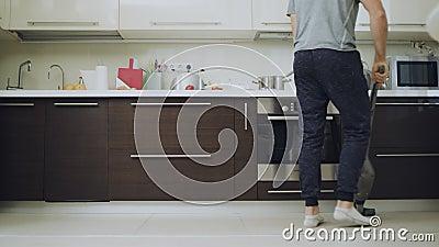 Φροντίδα ανθρώπου καθαρισμός δαπέδου με μηχανή κενού στη σύγχρονη κουζίνα απόθεμα βίντεο