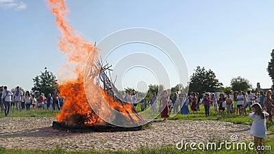 Φωτεινή εορταστική πυρκαγιά στο δασικό ξέφωτο, λαϊκοί εορτασμοί σε υπαίθριο στο πράσινο ξέφωτο, πλήθος των ανθρώπων κοντά μεγάλο  απόθεμα βίντεο